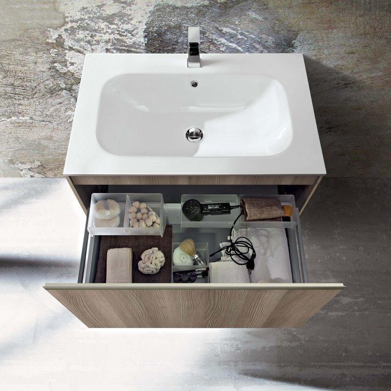 Particolare dell'ampio cassettone della base lavabo, organizzato con contenitori e divisori