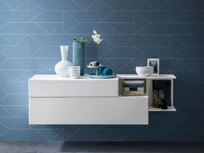 Cassettiera bianca sospesa su parete blu a disegni geometrici