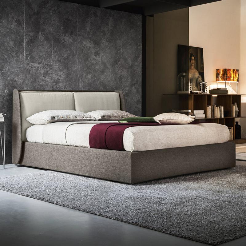 Letto Tayra in tessuto scuro inserito in camera grigia con parete grigia, pavimento grigio, tappeto grigio