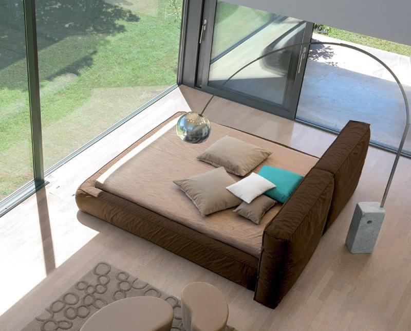 Il letto imbottito in piuma Fluff rivolto verso un'ampia vetrata è perfetto per godere comodamente del panorama