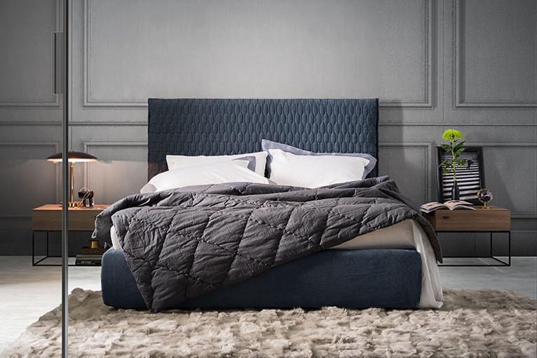 Camera con pareti grigie e letto blu con testiera trapuntata