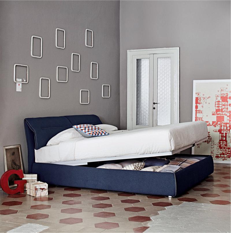 Per vivacizzare una camera grigia si può giocare con i colori degli arredi, come il blu del letto Campo