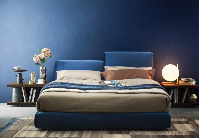 Camera da letto con pareti e letto blu in velluto