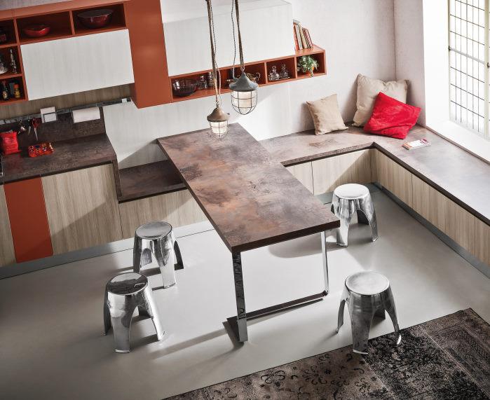 Dettaglio: la cucina bianca, arancio e legno è completata da tavolo e panca effetto ruggine