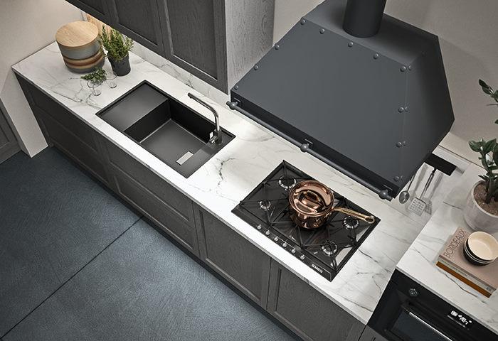 Cucina con piano in marmo ed elettrodomestici neri