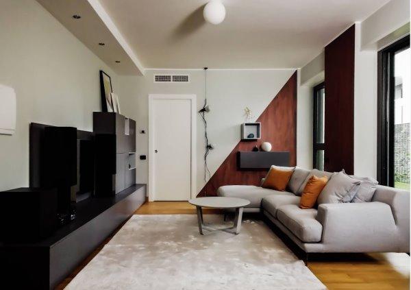 Parete attrezzata con porta tv sulla sinistra. Divano con penisola, tavolino e contenitori a parete sulla destra.