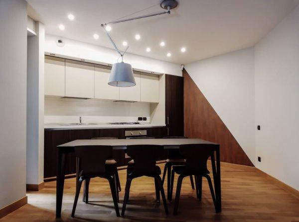 Cucina con mobili in legno chiaro e scuro. Tavolo con sedie. Parete decorata: metà color ruggine e metà grigia