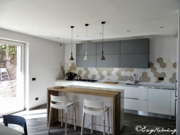 Foto: cucina bianca e grigia con ante a gola e isola con piano snack in legno massello