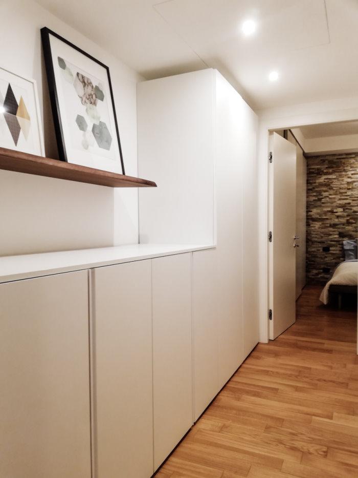 Foto dell'armadio in corridoio a progetto concluso. Armadio in laminato bianco con maniglie ad unghiatura verticali.