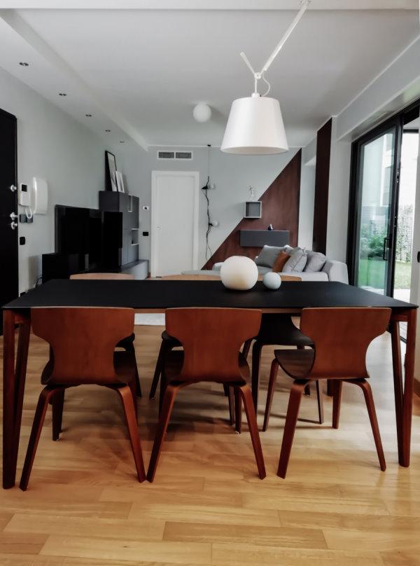 Fotografia scattata dalla cucina: tavolo e sedie in primo piano, zona relax sullo sfondo