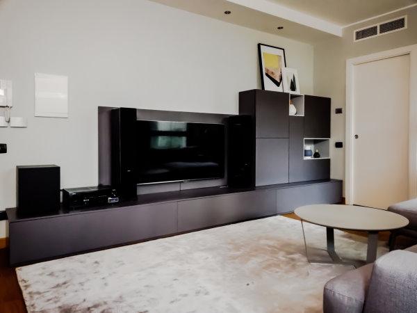 Dettaglio della parete attrezzata in grigio scuro con cassettoni, pensili contenitore e pannello porta tv