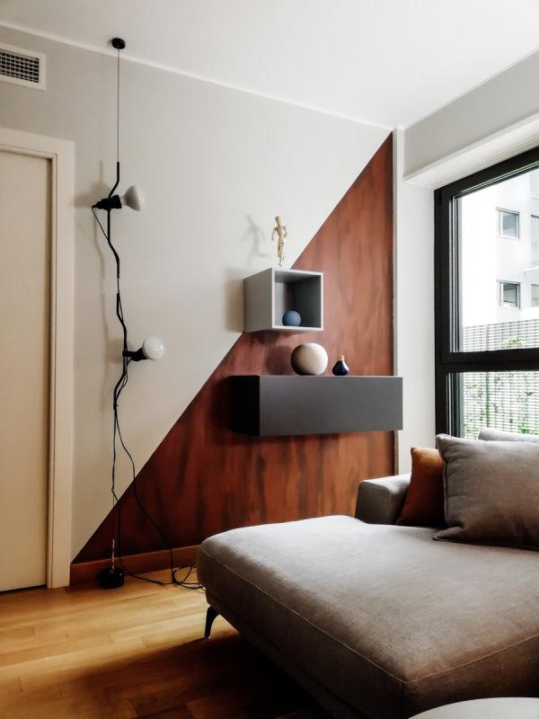 Dettaglio di una parete decorata color grigio ed effetto ruggine. Contenitori sospesi a parete.