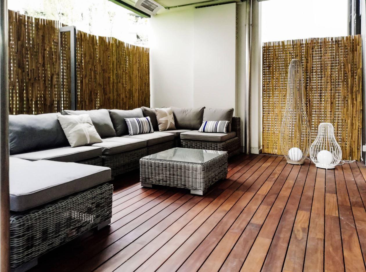 Veranda con divanetto da esterni, tavolino e lampade