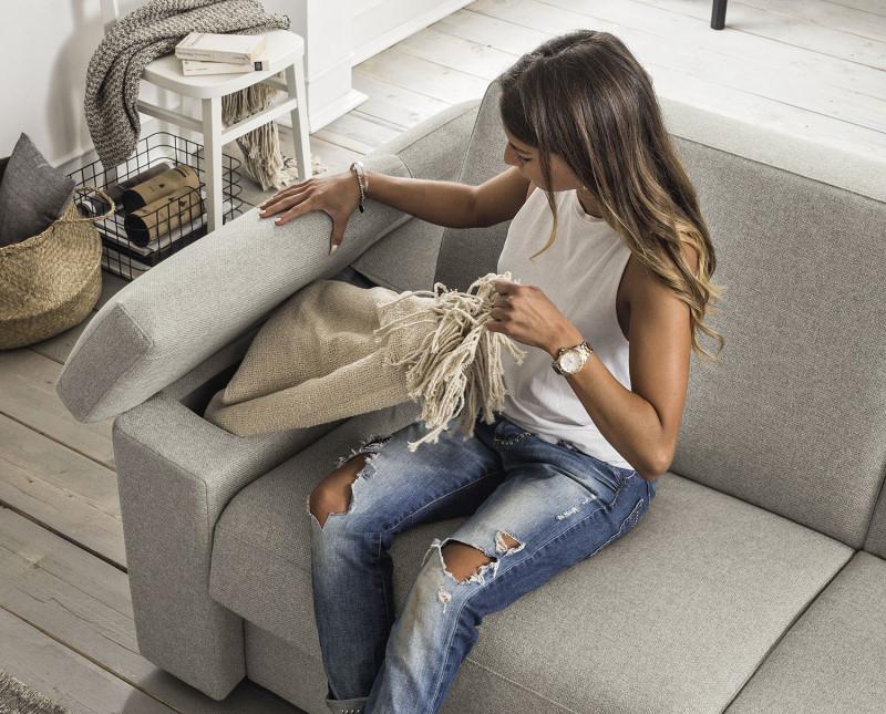 Il bracciolo si solleva e scopre un contenitore per coperte o cuscini extra