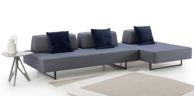 Divano design minimal in tessuto blu con piedi a slitta in metallo