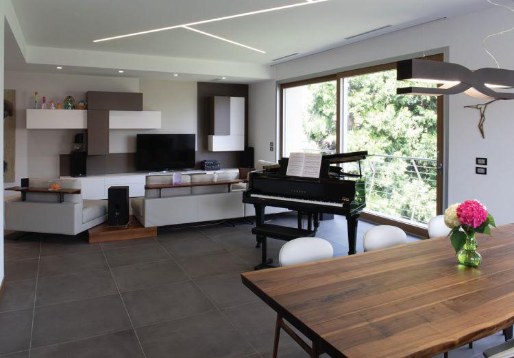 Open space con divano centrale con mensole integrate - Caen