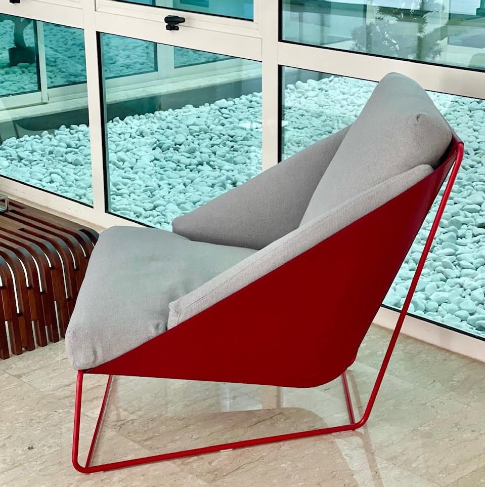 Angolo lettura con poltroncina di design e tavolino in legno curvato