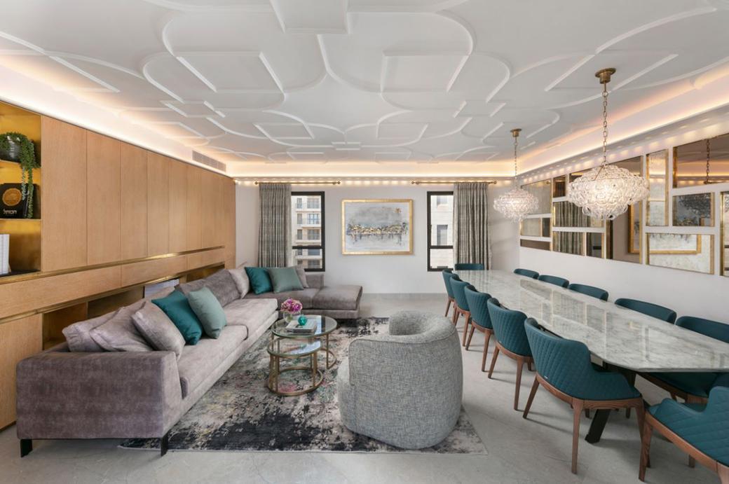 Ampio soggiorno-salotto con tavolo in marmo per 12 e divano in velluto con penisola