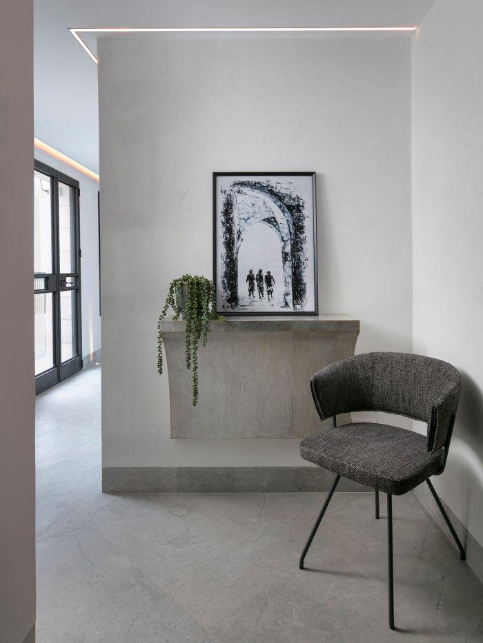 Corridoio con consolle sospesa stile minimal e poltroncina di design