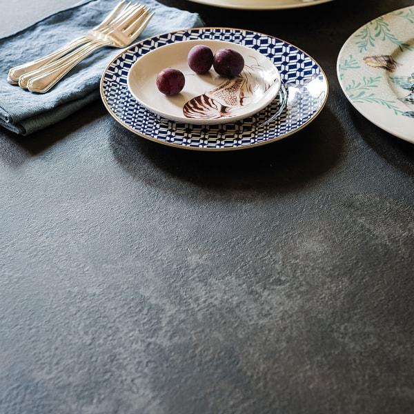 Dettaglio di un tavolo con piano in legno laminato effetto ossidato