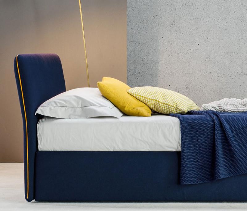 Letto singolo imbottito blu con profili e cuscini gialli