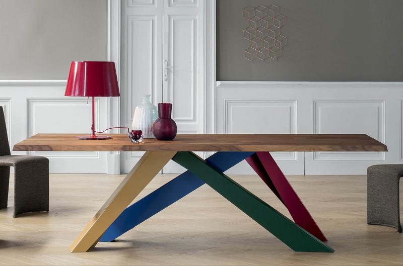 Tavolo di design in legno con gambe incrociate colorate